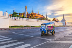 Thai Tuk Tuk and the Grand Palace. Tuk Tuk is parking in front of Wat Phra Kaeo or Grand Palace, Bangkok, Thailand. This is a beautiful scene of the palace with stock image