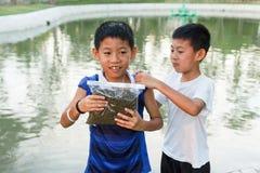 Thai twin boy prepare for feed fish. Royalty Free Stock Photos