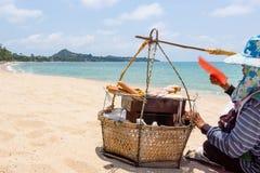 Thai vendor grills on sandy beach. Vendors basket on sandy beach Stock Image