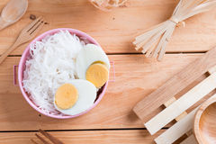 Thai vermicelli eaten with curry. Thai vermicelli and boiled egg eaten with curry on wooden background Royalty Free Stock Image