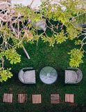 Thai vintage outdoor rattan chairs and glass table on glass lawn under tree stock photos