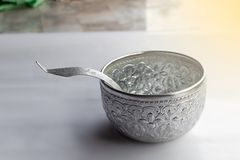 Thai water bowl and ladle silver on white background. Thai water bowl and ladle silver on table white background royalty free stock image
