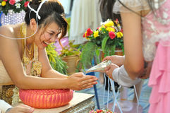 Thai Wedding. The bride is accepting the wishes from the  friends (Pouring water for new life Stock Images