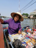 Thai woman in boat. BANGKOK- JANUARY 20,2013: Thai woman in boat sells food and souvenirs Stock Image
