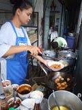 Thai woman cooking food, Thailand. BANGKOK, THAILAND - MAY 16: Thai woman cooking food in an outdoor kitchen May 16, 2005 in Bangkok Stock Photos
