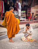 Thai woman gave aims and offering food to the monk. Royalty Free Stock Photos