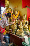 Thai Woman glid cover angel statue with gold leaf at Phra Kal Sh Royalty Free Stock Image