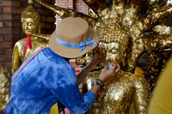 Thai Woman glid cover Buddha statue with gold leaf at Wat Yai ch Stock Photo