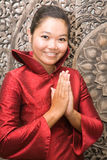 Thai woman greeting. Young Thai woman in red silk dress greeting Stock Image