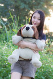 Thai Woman Hug Stuffed dog on in Grass Royalty Free Stock Photo