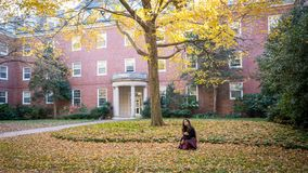 Thai woman kneeling in front of university building in the fall royalty free stock photo
