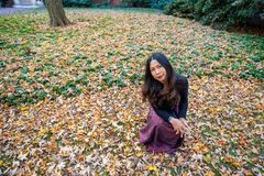 Thai woman kneeling on ground surrounded by leaves in the fall stock photo