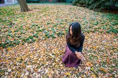 Thai woman kneeling on ground surrounded by leaves in the fall l royalty free stock image