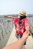 Thai woman lead someone by the hand and hold on the walkway bridge Royalty Free Stock Images