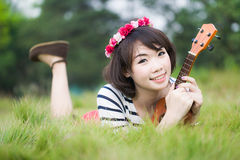 Thai woman lie and hug Ukulele in garden Stock Photography