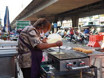 Thai woman makes sausage crepes at a local market Royalty Free Stock Photography