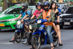 Thai woman moto taxi passenger. BANGKOK, THAILAND, February 15, 2015: A moto taxi is carrying a young Thai lady on his motorbike in the Sukhumvit road near the Royalty Free Stock Image