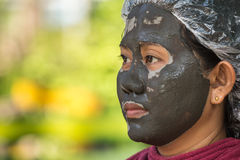 Thai woman with mud spa on her face on green blur background Stock Images