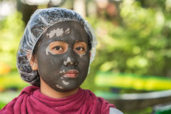 Thai woman with mud spa on her face on green blur background Royalty Free Stock Image
