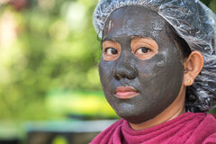 Thai Woman with mud spa on her face on green blur background Stock Image