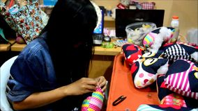 Thai woman Needlework or sewing cotton owl doll pillow. Needlework is a broad term for the handicrafts of decorative sewing and textile arts. Anything that uses stock video
