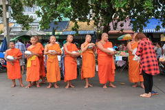 Thai woman is offering her food to Buddhist novices at Asaha Puja Day or Sangha Day Stock Photos