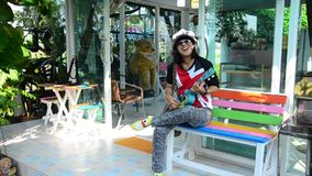Thai woman play Ukulele  or small Acoustic Guitar stock video