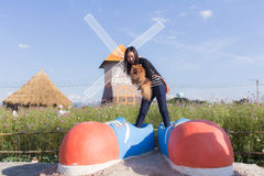 Thai woman and pomeranian with big shoes in cosmos field, Muangkaen Stock Photo