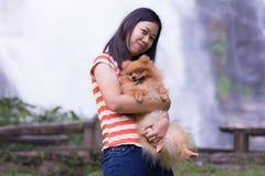 Thai woman with pomeranian at Wachirathan waterfall chiangmai Stock Photo