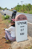 Thai woman portrait with Milestone go to DONTALAD at Pakse in Champasak, Laos. A milestone is one of a series of numbered markers placed along a road or boundary Royalty Free Stock Photo