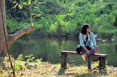 Thai woman portrait sit on bench at forest in Suan Phueng Royalty Free Stock Image