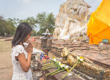 Thai woman praying in Ayutthaya temple in front the big buddha. Royalty Free Stock Image