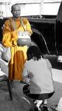 A Thai woman is praying at a monk`s feet in Bangkok.  Royalty Free Stock Photos