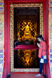 Thai woman praying with Reflection Golden buddha statue Royalty Free Stock Photos