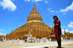 Thai woman praying of Shwezigon Pagoda or Shwezigon Paya in Bagan, Myanmar. Shwezigon Pagoda or Shwezigon Paya is a Buddhist temple located in Nyaung-U, a town Royalty Free Stock Photos