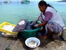 Thai woman preparing seafood, Thailand. KOH PHANGAN, THAILAND - JANUARY 4: Thai woman prepares fresh squid by the ocean on January 4, 2005 in Koh Phangan Stock Photo