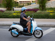 Thai woman rides a scooter. Editorial only. Royalty Free Stock Photography