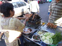 Thai woman selling cooked sausages, Thailand. Royalty Free Stock Image