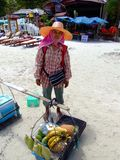 Thai woman sells food on the beach, Thailand. KOH SAMUI, THAILAND - JANUARY 21: Thai woman sells fruit and sweetcorn to tourists on January 21, 2005 in Koh Royalty Free Stock Image