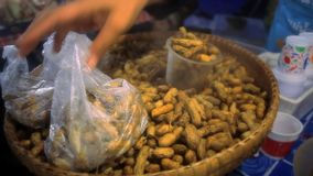 Thai woman sells pack of hot nuts in their skins stock video footage