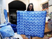 Thai woman sewing handmade tablecloth from indigo frabric natural color in night time at home. On July 12, 2017 in Nonthaburi, Thailand royalty free stock images