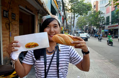 Thai woman show french loaf or baguette sandwich Stock Image