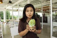 Thai woman show melon ice cream before eating at Cafe. And restaurant in Thailand stock images