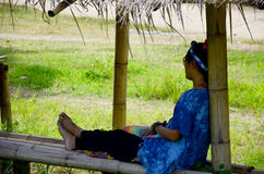 Thai woman sit and rest in the hut at  Baan Natong village. In Phrae, Thailand Royalty Free Stock Photo