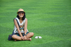 Thai woman sitting on artificial turf at garden in Kanchanaburi Thailand. Royalty Free Stock Photography