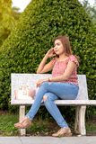 Thai woman sitting on a chair near the bush royalty free stock image