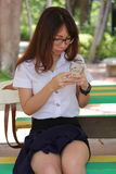 Thai woman student university beautiful girl using her smart phone. Stock Photos