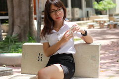 Thai woman student university beautiful girl using her smart phone. Stock Images