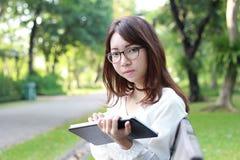 Thai woman student university beautiful girl using her tablet. Stock Photos