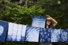 Thai women tie batik dyeing handkerchief indigo color. Thai woman tie batik dyeing handkerchief tie batik indigo color or mauhom color and hanging process dry royalty free stock image